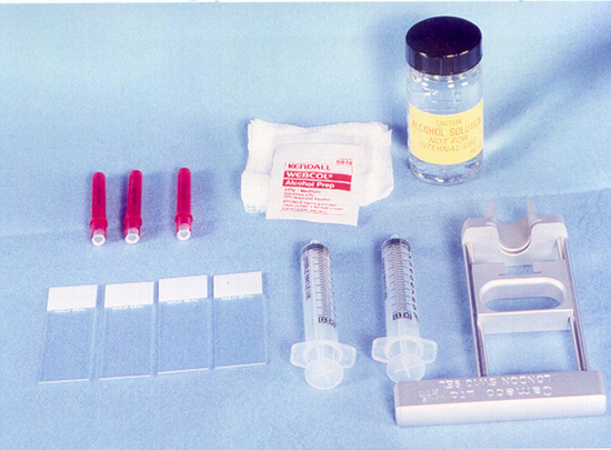 Figure 1. FNA biopsy equipment is simple and inexpensive. It includes an alcohol wipe; 4×4-inch gauze pads; 10-mL plastic syringes; 27-gauge, 1.5-inch stiff, noncutting, bevel-edged needles; spinal needles; glass slides; alcohol bottles; and a pistol-grip mechanical syringe holder.